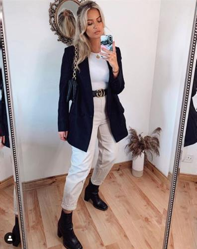 Irish influencer Melissa Riddell taking a selfie in a black blazer, khaki pants, and black boots