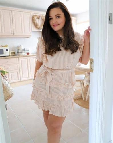 Irish influencer Catherine Carton posing in her kitchen in a pink and white dress with a ruffled skirt