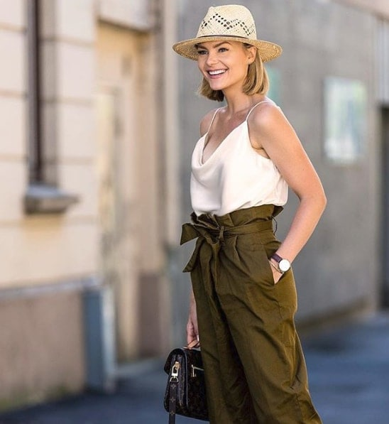 Influencer Caroline Berg Eriksen wearing straw hat and high waisted olive green pants