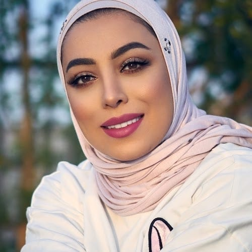 Bashayer Jomah wearing a pink hijab and a white long sleeve cover with pink art in front of a forest