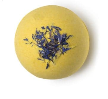 Yellow spherical bath bomb with purple flowers inside