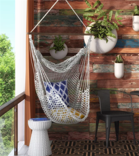 Chair hammock with blue and yellow pillows in it hanging from ceiling of room