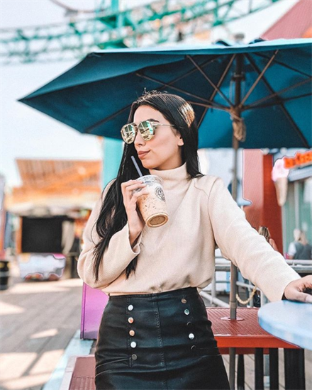 Influencer Claudia wearing beige turtleneck top and black leather skirt holding plastic coffee drink