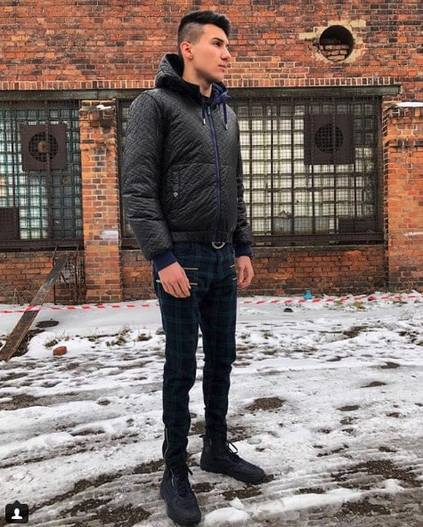 Influencer Filip Hoinkis wearing black puffy coat and plaid pants in the snowy street