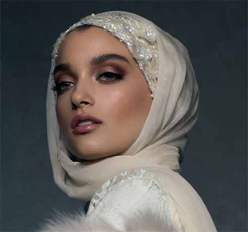 model wearing ornate pearl hijab in ivory against a dark backdrop
