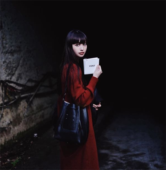 Influencer Emi Suzuki wearing long red coat under a dark tunnel