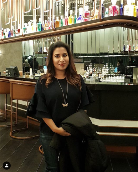 Kuwaiti food and fashion blogger, Mimi, standing in front of a bar