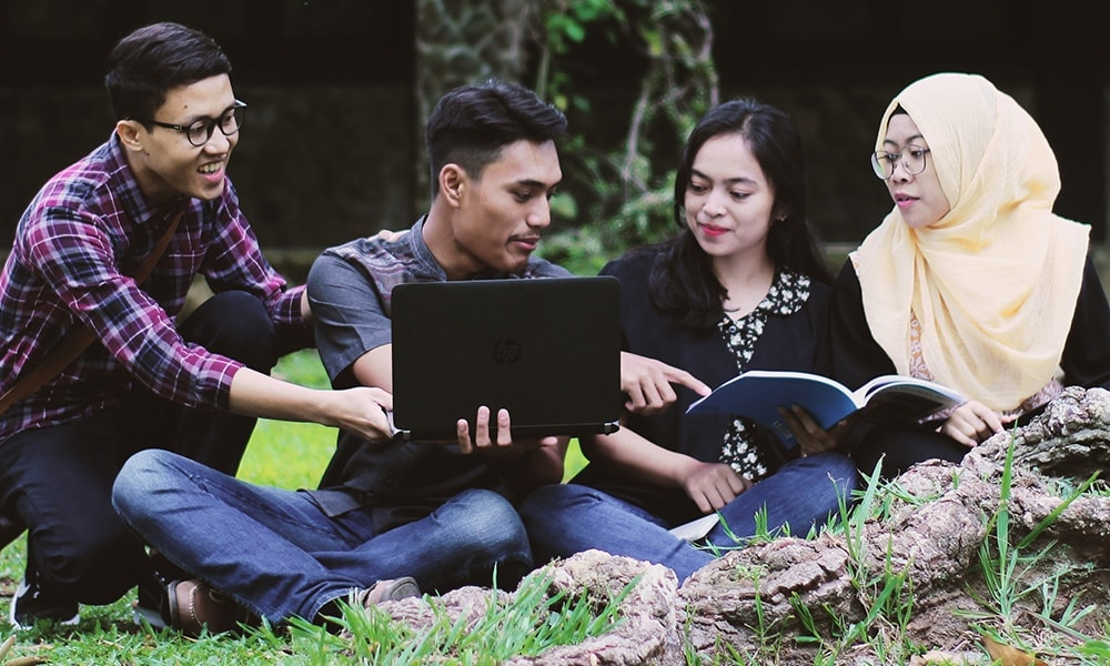 Four children sitting in grass studying