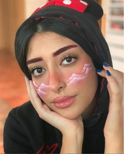 Bahraini pro makeup artist and influencer Fatema AlMuhana with artistic clouds painted on her cheeks
