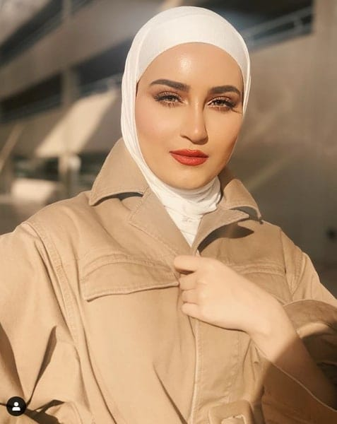 Dalal AlDoub in tan trench coat and white hijab