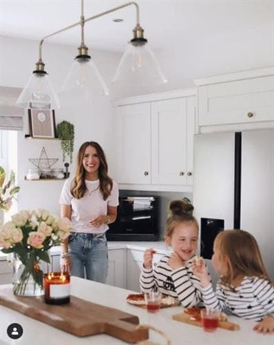 Irish blogger and influencer Anna smiling for the camera in her kitchen with her two daughters