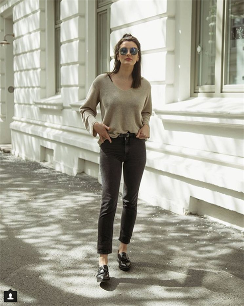 Influencer Line Kirkhus wearing black jeans and cream sweater outside