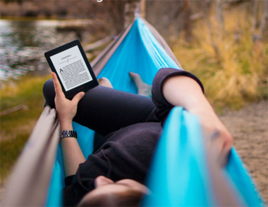 Person laying in blue hammock holding up black kindle