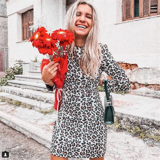 Fashion Blogger Oanna Popa wearing cheetah print dress holding red daisies