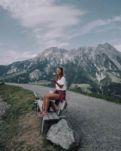 Austrian blogger Nina Radman sitting on a bench in the Alps