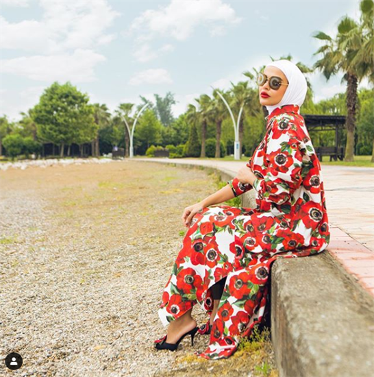 Kuwaiti fashion and beauty blogger Mariam Mohammad sitting on a beach in a floral dress